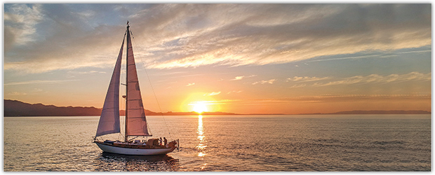Celeste under sail at sunset